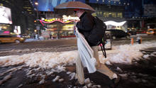 A businessman carries an umbrella and a dress shirt on a hanger while making his way through slush and snow in New York's Times Square Feb. 5, 2014.