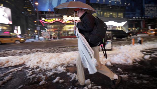商人在挂衣架运载一把伞和一件男式衬衫,当做他的方式通过融雪和雪在纽约时代广场2014年2月5日时。