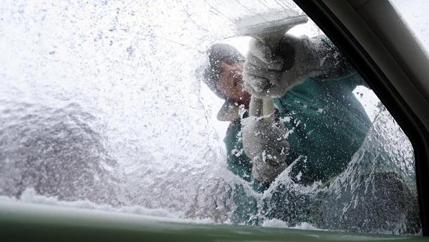 特里吉利斯于2014年2月12日在阿拉巴马州佩恩堡的汽车窗外擦掉冰。