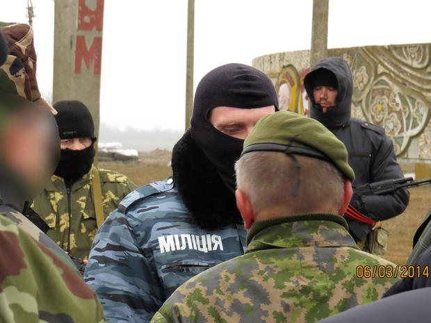 Two members of an Organisation for Security and Cooperation in Europe (OSCE) military observer mission (facing away from camera) are stopped at the Crimean border by unknonw armed men