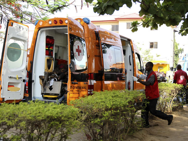 A Red Cross worker runs towards an ambulance carrying victims of a bomb blast at the Asokoro General Hospital in Abuja