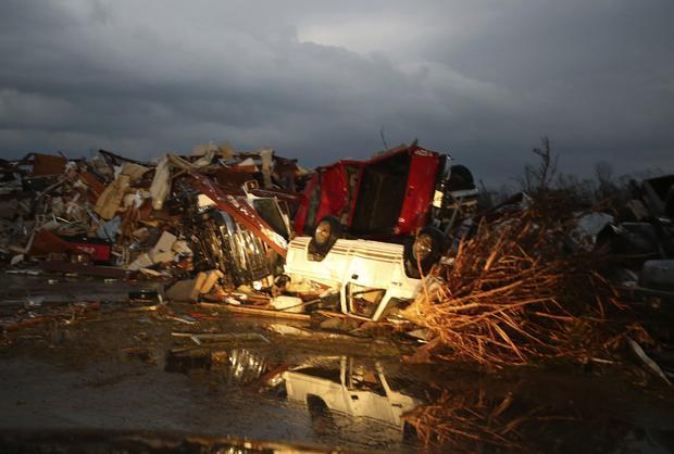 龙卷风摧毁了阿肯色州五月花镇后,翻转的皮卡车在水中反射出来