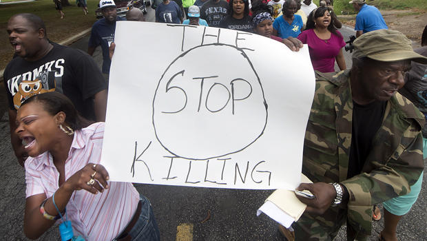 K.K. Davis, left, and Tommy Jones of Hearne, Texas, carry a sign with other protesters outside the Hearne Police Department May 8, 2014, following the shooting two days earlier of a 93-year-old woman.
