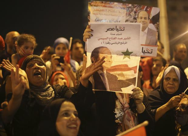 Supporters of Abdel-Fattah el-Sissi hold poster of him as they celebrate at Tahrir Square in Cairo on May 28, 2014