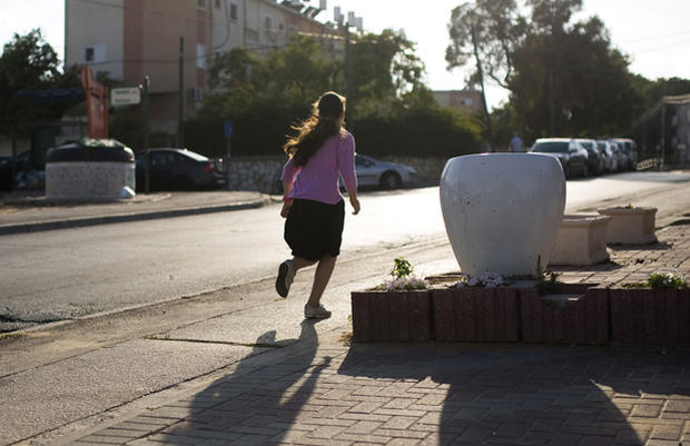 An Israeli girl runs as a siren sounds warning of incoming rockets in the southern city of Ashkelon