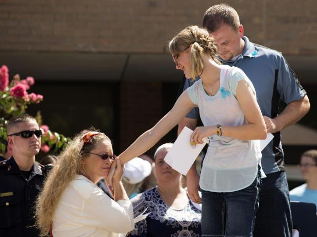 2014年7月12日,在德克萨斯州春天,一个支持者迎接Cassidy Stay,这是她父母和兄弟姐妹大规模射击的唯一幸存者,在庆祝Lemm小学的Stay家庭生活的社区纪念馆。