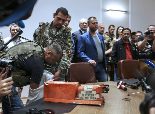 """A pro-Russia separatist shows members of the media a """"black box"""" from Malaysia Airlines flight 17, before handing it over to Malaysian representatives during a press conference in Donetsk"""