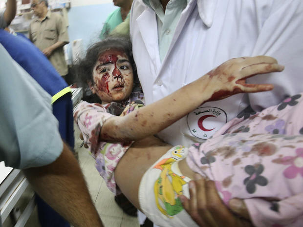 A Palestinian medic carries a girl who medics said was wounded by Israeli shelling, at a hospital in Khan Younis in the southern Gaza Strip