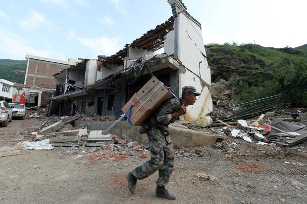 A rescue worker carries relief supplies to a remote village in disaster-hit Ludian county in Zhaotong, southwest China