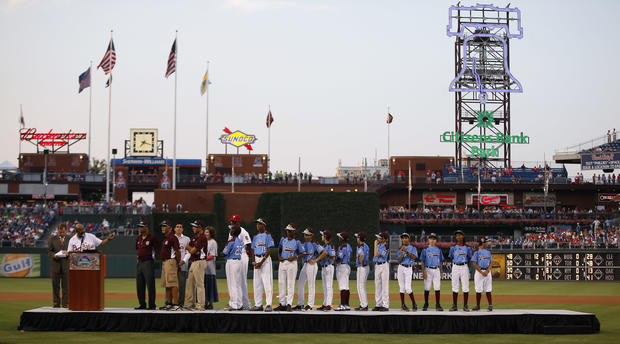 Members of the Taney Dragons baseball team listen to Philadelphia Mayor Michael Nutter speak during a tribute to celebrate the youth team's accomplishments before a baseball game between the Philadelphia Phillies and the Washington Nationals Aug. 27, 2014, in Philadelphia.
