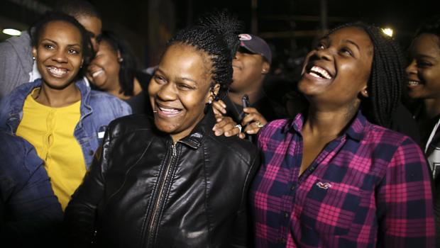 家庭成员围绕Keisha Gaither,左边第二,绑架受害者Carlesha Freeland-Gaither的母亲,他们在2014年11月5日在费城举行的新闻发布会上庆祝,调查人员宣布Freeland-Gaither被发现安全出局