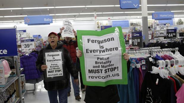 2014年11月28日,在密苏里州弗格森附近的黑色星期五,示威者抗议迈克尔·布朗的枪杀事件,他们走过当地一家沃尔玛商店。