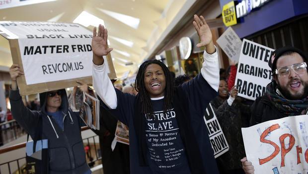 2014年11月28日在密苏里州圣路易斯举行的黑色星期五,示威者抗议迈克尔·布朗的射击死亡标志着他们穿过圣路易斯商业街购物中心大喊大叫。