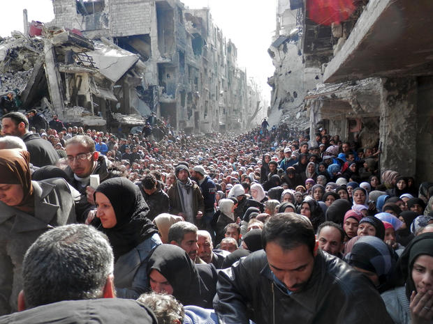 Residents wait in line to receive food aid distributed in the Yarmouk refugee camp in Damascus
