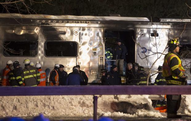 紧急工作者在2015年2月3日在纽约Valhalla的被烧毁的地铁北部铁路通勤火车及其附近站立