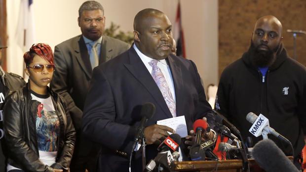 中心律师达里尔·帕克斯(Daryl Parks)与记者谈话,莱斯利·麦克斯帕登(Lesley McSpadden)和迈克尔·布朗(Michael Brown),18岁的迈克尔·布朗(Michael Brown Jr.)的父母,于2015年3月5日在密苏里州戴尔伍德举行的新闻发布会上倾听。