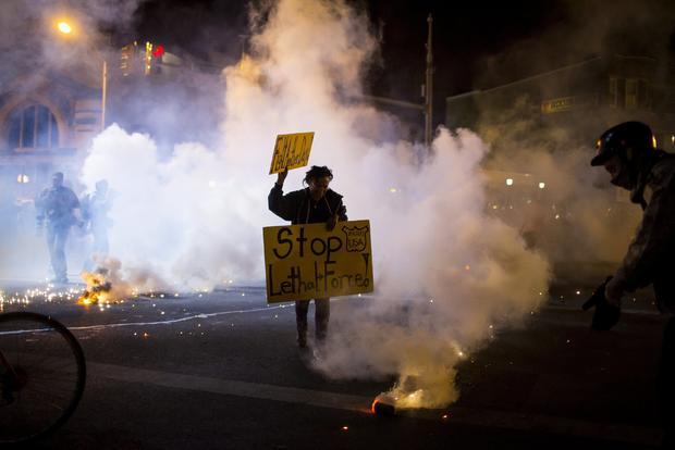 2015年4月28日星期二晚上全市宵禁在巴尔的摩生效后不久,抗议者举起烟雾和人群控制特工上升的标志