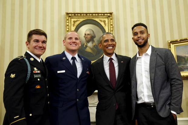 奥巴马总统与斯宾塞·斯通,第二名左边的安东尼·萨德勒和左边的阿莱克·斯卡拉托斯合影留念,他们是8月份在华盛顿白宫椭圆形办公室制服枪手的三名男子。2015年第17期。