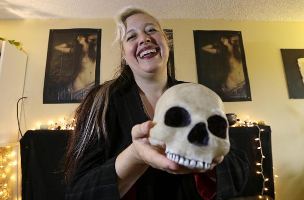 莉莉丝斯塔尔是西雅图撒旦神庙的分会负责人,她在2015年10月28日在西雅图的家中拍摄时拍摄了一块塑料头骨。