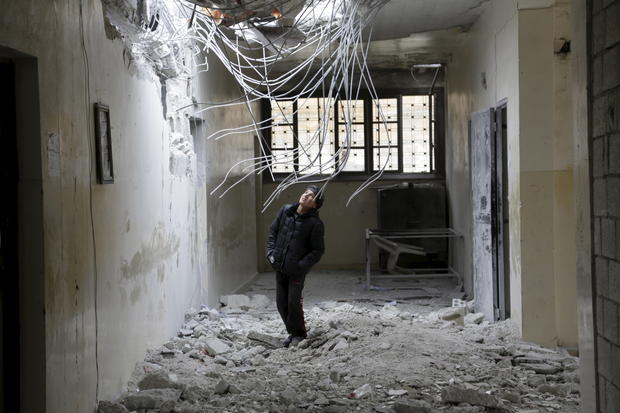 A boy inspects damage inside his school due to what activists said was an airstrike carried out by the Russian air force in Injara, Syria, Jan. 12, 2016.