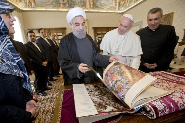 Iran President Hassan Rouhani exchanges gifts with Pope Francis at the Vatican
