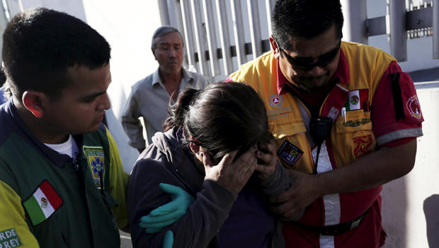 An inmate's family member is helped by a Green Cross worker and a Civil Protection worker outside the Topo Chico prison in Monterrey, Mexico, Feb. 11, 2016.