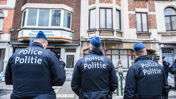 Three police officers stand guard at the Meiser neighborhood in Schaerbeek in Brussels on March 25, 2016, during an anti-terrorist operation searching for suspects of the Brussels terrorist attacks.