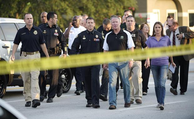 2016年6月12日,在佛罗里达州奥兰多的Pulse夜总会发生致命枪击事件后,奥兰多市长Buddy Dyer,中间右侧,以及奥兰多警察局长John Mina,左中锋,抵达新闻发布会。