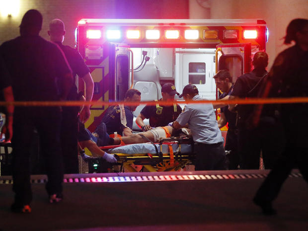 Emergency responders administer CPR to an unknown patient on a stretcher as law enforcement officials stand nearby at the emergency receiving area of Baylor University Medical Center, early July 8, 2016, in Dallas.