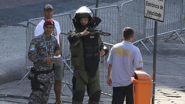 An agent of the bomb squad in protective clothing stands in the area near the finishing line of the men's cycling road race at the 2016 Rio Olympics after they made a controlled explosion, in Copacabana, Rio de Janeiro, Brazil, August 6, 2016.