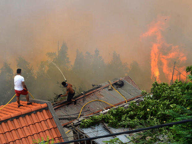 Men spray water on the roofs of houses to protect them from an approaching fire in Portugal's Maderia islands