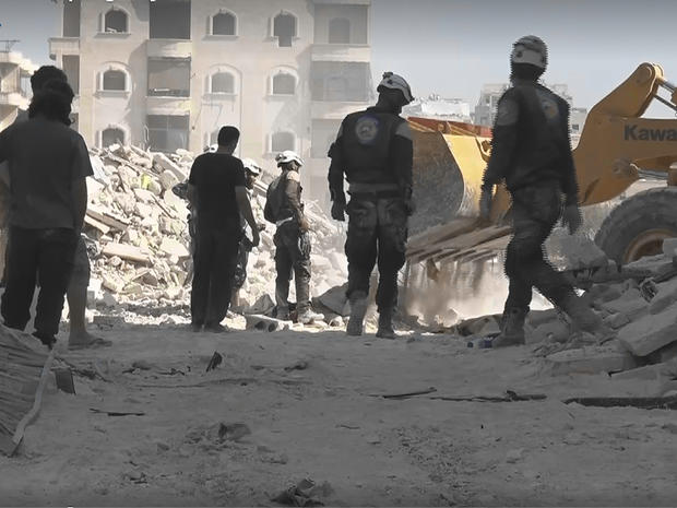 An images from the Syrian activist Thiqa Agency group shows civil defense rescue workers at the scene of an alleged airstrike on a women and children's hospital in the rebel-held town of Kafr Hamra, in northern Aleppo