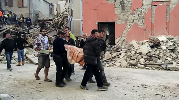This still image taken from video shows rescuers recover a victim from a crumbled building in Amatrice