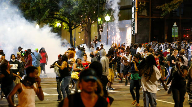 People run from flash-bang grenades in uptown Charlotte, North Carolina, during a protest of the police shooting of Keith Scott in Charlotte Sept. 21, 2016.