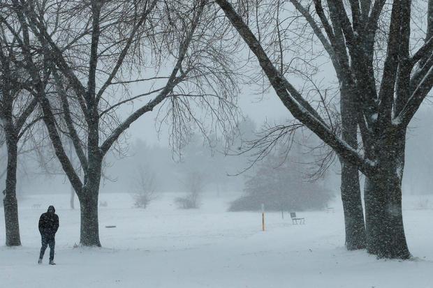 2017年1月7日,马萨诸塞州梅德福的冬季风暴期间,一名行人穿过雪。
