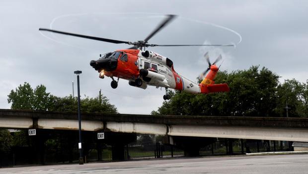 美国海岸警卫队一架载有撤离人员的直升机在飓风哈维淹没德克萨斯海湾沿岸的雨水引起广泛的洪水之后,在乔治布朗会议中心附近降落。