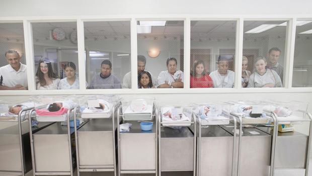 观看婴孩的新的父母在医院托儿所