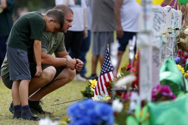 送葬者在一个临时纪念碑上祈祷,以纪念在圣达菲圣达菲高中枪击事件中遇难的遇难者