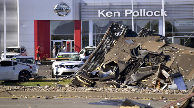 Debris and damaged vehicles sit in front of a car dealership on June 14, 2018, in Wilkes-Barre Township, Pennsylvania.