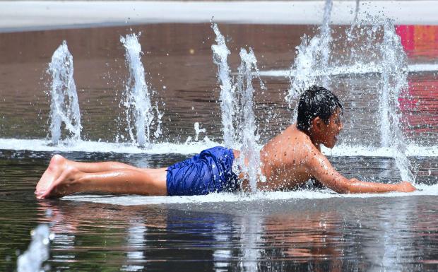 2018年7月5日,一名男孩在加利福尼亚州洛杉矶的大公园的水上游乐区冷却,在洛杉矶地区发生热浪之前。