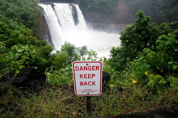 在Hilo的飓风巷,雨水冲刷的瀑布上有一个标志警告危险