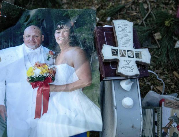 2019年3月4日,在阿拉巴马州Beauregard,一场龙卷风摧毁了他们的房子,Carol Dean和David Wayne Dean的婚礼照片中,Carol Dean在一堆个人物品中找到了他们的残骸。