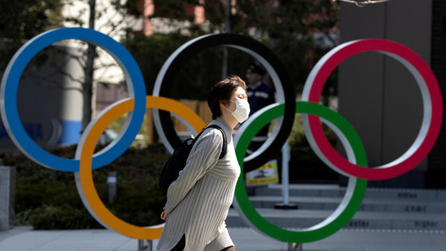 A woman wearing a protective face mask amid an outbreak of the coronavirus disease COVID-19 walks past the Olympic rings in front of the Japan Olympics Museum in Tokyo, Japan, March 13, 2020.