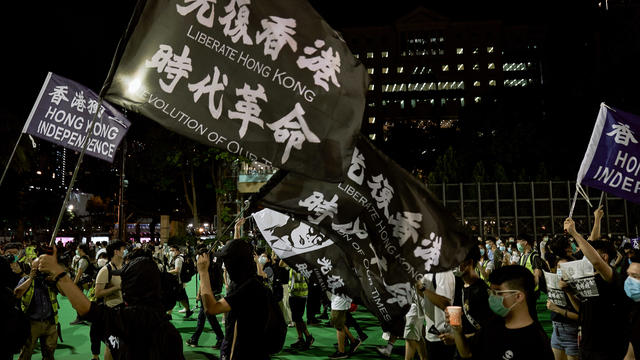 Protesters hold flags while chanting slogans during the 31st