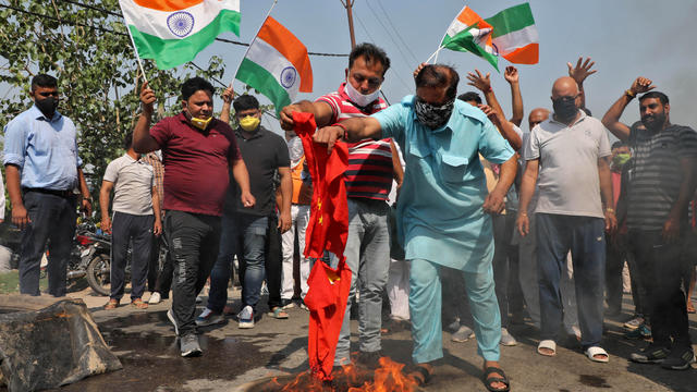 Demonstrators burn a flag resembling Chinese national flag during a protest against China, in Jammu