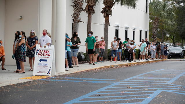 People line up at a polling station as early voting begins in Florida
