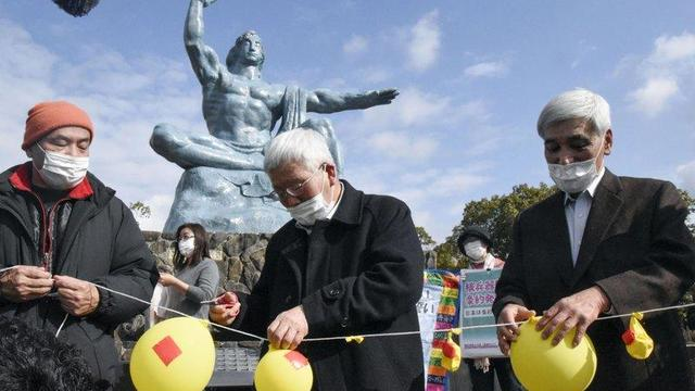 Participants deflate balloons in hope of neutralizing and demolishing nuclear warheads, during a memorial gathering at Peace Park in Nagasaki, southern Japan Friday, Jan. 22, 2021.
