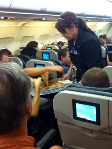 A Frontier Airlines flight attendant passes out pizza to passengers aboard a Denver-bound flight diverted to Cheyenne, Wyo., July 7, 2014. The airplane pilot treated his passengers to the pizza after they were diverted.
