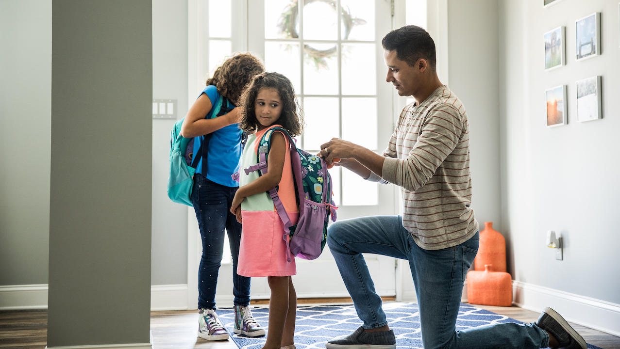 Father packing daughters backpacks for school