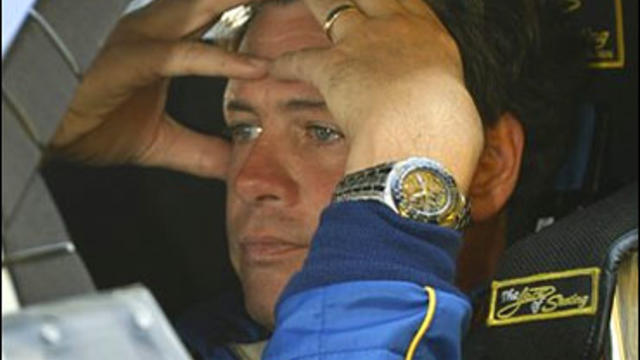 NASCAR driver Michael Waltrip waits in his car before the start of practice